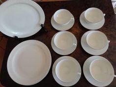 Tias Eckhoff (f. 1926) for Porsgrund Porselensfabrikk, 'Det riflede' teservise, 1950-tallet. Hvit porselen med riflet overflate og sølv rand, bestående av asjetter og tekopper med skåler, komplett til seks. En ekstra tekopp med liten sprekk følger med. Mål kopper Ø=10 cm H: 5,5cm, skåler/asjetter Ø: 14 og 21,5 cm. Tekopp med skål i produksjon fra 1952. Med serviset 'Det riflede' vant Tias Eckhoff gullmedalje ved Triennalen i Milano i 1954 og i 1965 'Merket for god design' for det samme.
