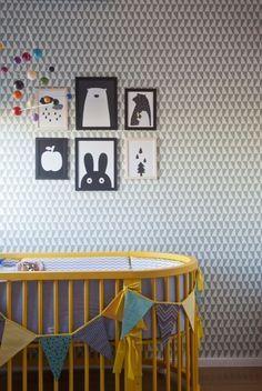Esse quarto tem 8 m², foge de temas, abusa do cinza e preto, e esbanja charme. O berço oval amarelão garante o contraste com o papel de parede, da papeldeparededosanos70.com. O os quadros foram garimpados na web pela Tatiana Machado, da Elefante Design.