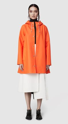 The Mosebacke Burnt Orange raincoat is the women's A-line version of our iconic raincoat. This feminine model has a fashion forward silhouette, with a spacious cut. It is handmade in rubberized cotton, comes unlined and with welded seams. The finest craft