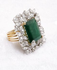Unique and aesthetic masterpiece made of emerald surrounded with exquisite diamonds set in orbs of gold.