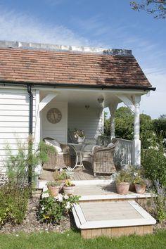 Cozy porch.. wicker chairs... flower pots. Cottage.. farmhouse