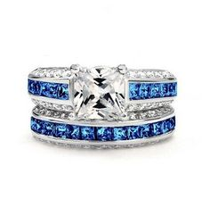 Spoiled Princess - Blue These flawless blue topaz fill the center line of both bands and mark the top of the engagement band with the large princess cut cubic zirconia. The sides of each band hold smaller white topaz that wrap around the blue. In a 10k white gold filled setting, this beautiful princess cut ring is perfect as an affordable wedding set, or to wear in place of your own set while on vacation. #alternativeweddingrings #shopcloverkitty #wedding #rings #engagement