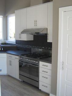 Modern Kitchen white Cabinets with black tile back splash