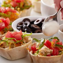 Mini chicken taco bowls are a snap to make when you use Perdue Short Cuts carved chicken breast. Top as you like with lettuce, tomato, olives and sour cream.