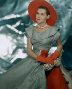 Georgia Hamilton wearing light grey dress with wide round collar, full skirt, and orange hat and gloves, 1949    Photo by Clifford Coffin