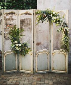 vintage screen ceremony backdrop decorated with airplants and blooms