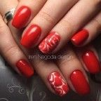 Red and white rose nail art design. The nails use a bright red color as the main polish while detailing the outlines of the roses creatively using the white polish which also doubles as a background for some of the nails.