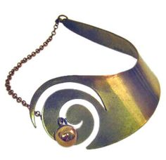 Sculptural brass collar with spiral and ball  Inspired by surrealism, biomorphicism, & primitivism, Art Smith's jewelry is dynamic in its size and form. Although sometimes massive in scale, his jewelry remains lightweight and wearable. Trained at Cooper Union, Art Smith, an African American, opened his first shop on Cornelia Street in Greenwich Village in 1946. He is one of the leading modernist jewelers of the mid-twentieth century.