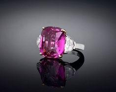 "Pink Ceylon Sapphire Diamond Ring. An extraordinarily rare, 16.37-carat Pink Ceylon sapphire takes center stage in this striking ring. Displaying the perfect purplish-pink or ""bubblegum"" hue for which the finest pink sapphires are so beloved, this enchanting, cushion-shape gem boasts both crystal-clear clarity and grand size. This jewel is supported by two shield-cut diamonds, totaling 2.06 carats.. Set in platinum and 18K yellow gold."