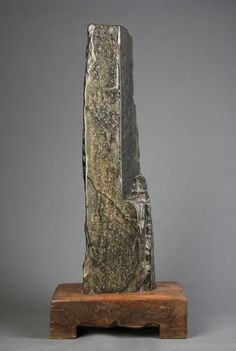 A Chinese Scholar's Rock A solid block of black Jade on an original wooden Ming stand China, 15th Century Rock: Height: 97cm