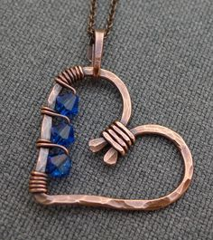 The heart pendant on this necklace is hand formed from copper wire and hammered for a textured look. I have wrapped the heart with smaller copper and 4mm capri blue swarovski crystal beads. It has been oxidized and then polished to bring back some of the copper color. It is hanging from an oxidized chain with a handmade clasp and measures about 16 1/2 inches long.    Please contact me with any questions.    Thanks for looking.
