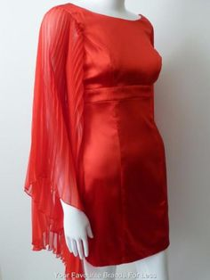 Guess-by-Marciano-Size-Small-Red-Silk-Short-Dress-With-Long-Pleated-Sleeves If you don't want to attract attention, don't buy this dress! This is a stunning red silk cocktail dress from Guess by Marciano. It has a round neckline, empire waist and strategic darting and seam work to flatter the figure. It has a low cut square back with an invisible zip and hook and eye closure. The stand out feature is the long, pleated kimono sleeves. The main body of the dress is fully lined.