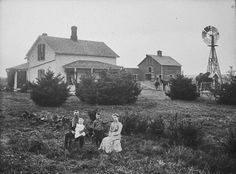 Family in front of two-story frame farmhouse in Buffalo County, Nebraska.
