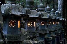 Row of lighted stone lanterns in the Okunoin Temple cemetery at Koyasan (Mount Koya), Wakayama, Japan