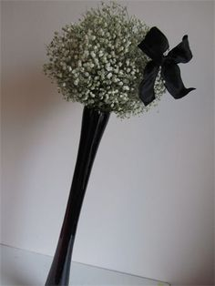 Tall Black & White Table Centres : Tall black vases with balls of white Gypsophilia and 'Cute' Bow.