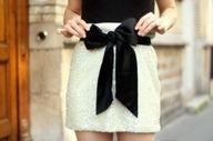 Jupe courte écrue ou blanche et un gros noeud noir en gros grain ou ruban