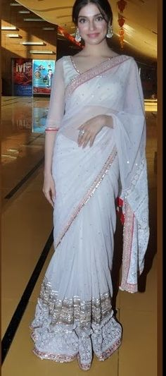 White designer embroidery net saree. Embroidered mirrors work all over saree and through out border. White embellished applique patch and gold thread work around the border. Paired with white designer quarter sleeves saree blouse with round neck pattern.