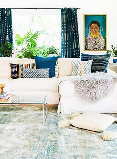 Living room with varying vintage indigo prints, a white sectional, and a faux sheepskin throw