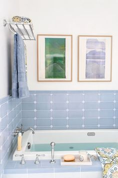A modern, boxy tub has a broad deck for toiletries and a separate handshower to accompany the wall-mount shepherd's crook faucet. Towels hang within reach from 