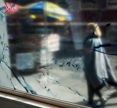A passerby reflected in a street window. Color photography.