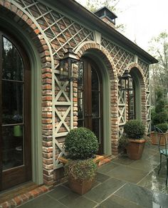 Brick, trellis and round boxwood home exterior decor.
