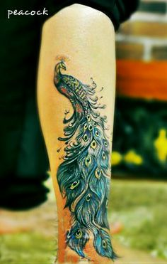 a gorgeous peacock tattoo on the leg with beautiful feather #peacock #feather