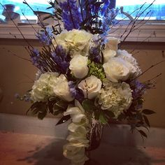 Centerpiece of white roses, white hydrangea and blue delphinium with birch branches and strung rose petals..  Doristhefloristt.com