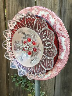 Vintage red and clear glass gets new life as a flower to be displayed and enjoyed by everyone! There is a spoon attached to the back that inserts into a pole, which to save you money on shipping cost, can be purchased at any hardware store. They are usually 4 to 5 ft. tall and 3/4