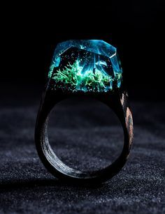Ocean Oasis Ocean Oasis  Where land ends and the ocean bends, hillsides become teal tides.   This ring is made of teal resin and bits of moss. The base is wenge wood, a tropical timber which is both heavy and hard