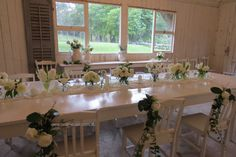 Elegant tablescape of white flowers in vases,  candles, material table runner, chair posies. The intimate and rustic reception room is dressed ready for place settings to finish it off. Barn reception, rustic, country, classic white