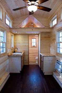 Interior of tiny home maximizes space, with small bathroom next to kitchenette. Light natural wood over dark hardwood flooring throughout.