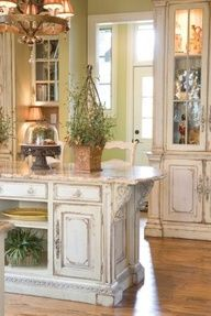 Amazing kitchen ~ Wearing a distressed style. Light green walls, wood floors, antique white cabinets