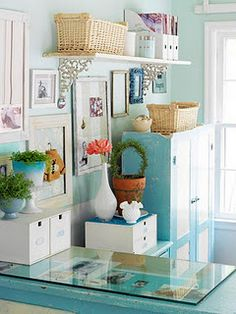"To give more storage room, move it up the wall, into containers or out the door.  This room has what is deemed Beautiful Clutter. A lot of ""stuff, but it is contained, shelved and the white brightens the room and give a clean, clear impression."