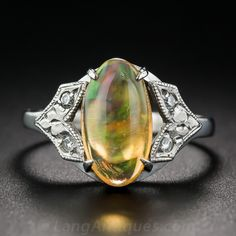 A kaleidoscopic play of honey and green, with flashes of reddish-orange and yellow, inhabit this exotic cabochon jelly opal presented in restrained Art Deco fashion between glittering diamond-set chevrons. A party for your pinky! (or any other finger). Circa 1930s.