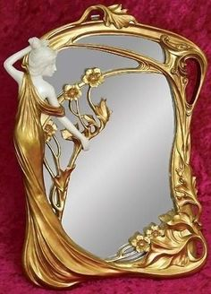 Art Nouveau Style Mirror. Made with cold cast resin & hand-painted, this exquisitely detailed piece features a characteristic curving, flowing form. Cream colored simulated animal tusk & antiqued gold finish.