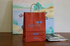 Bolsas impresas y asas de cartón.