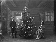 Nordic Christmas with candles and candle holders on the tree - a studio photograph from the early 1900s or late 1800s.  Candle clips, tea light candle holders and Christmas tree candles available from www.christmasgiftsfromgermany.com