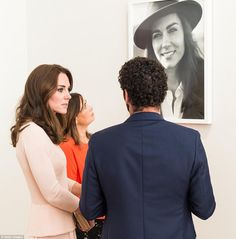 Kate stands next to the cover image for her Vogue debut, which shows her wearing a brown s...