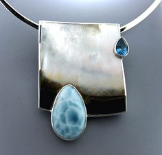 The large teardrop is Larimar and the smaller looks like a London Blue topaz set on a Mother of Pearl backdrop and then set in Sterling Silver.