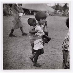 W. Eugene Smith, Girl with baby brother tied on her back carrying bottle, 1944