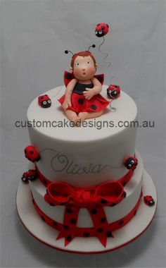 This cake was made for a special friend  Little Olivia is turning 1 on the weekend and her mum is having a ladybird themed party. The only requirements for this cake were that it had to be red, white and black  other than that  I had free reign on the design. I decided to make little Olivia dressed in a ladybug outfit on top of a cake surrounded by ladybirds.