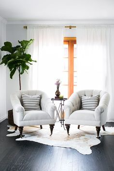 Beautiful tufted chairs + cowhide rug + brass curtain rod with white panels + fig tree