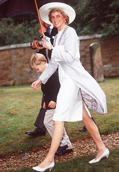 Princess Diana - 1989 Diana attended a U.K. wedding in a white sheath dress and dove-gray coat accessorized with a traditional British wedding hat-and an even more traditional British umbrella!