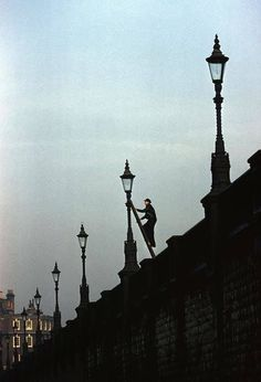 A Lamplighter doing his rounds, London, 1962.