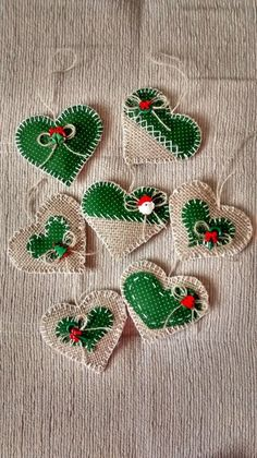 handmade Christmas ornaments ... hearts made of burlap in natural and bright green ... blanket stitch edges ... #feltcrafts