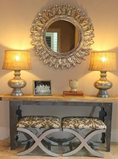Good example of mixing textures.  A little bling from the mirror and lamps on a weathered console. Nice.  I love using stools like these that can be tucked away or pulled out to use.