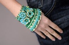 Green - turquoise crochet bracelet with crocheted flowers.
