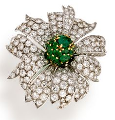 A diamond and emerald brooch, Schlumberger for Tiffany & Co.  the realistically designed flower centering a stamen of pavé-set circular-cut emeralds within petals of pavé-set round brilliant-cut diamonds; signed Schlumberger and Tiffany & Co.; estimated total diamond weight: 9.00 carats; mounted in platinum; length: 1 3/4in.