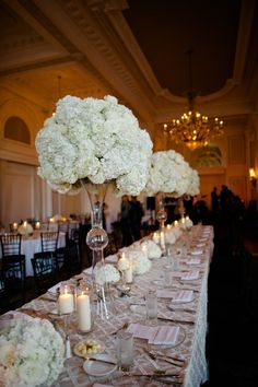 Bridal party seating at estate table with tall vases of all white florals. Flowers by @Jade Lee of Lovelee Affairs.