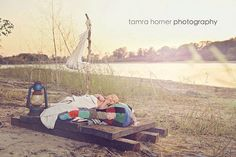 Durant, Oklahoma newborn and baby photographer. Baby laying on wooden raft at lake. Outdoor newborn photography